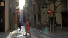 View to small cobbled street in Valencia, Spain. VALENCIA, SPAIN - JULY 15, 2016: View to narrow cobbled street with traffic prohibited sign, zebra crossing and stock footage