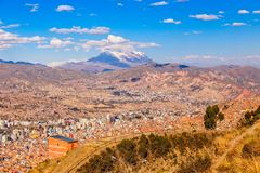 View to the snow cap of Illimani peak and valley full of living houses, El Alto, La Paz city, Bolivia stock photos