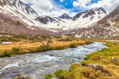 View to snow on Caucasus mountains over clear water stream near Royalty Free Stock Photo