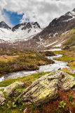 View to snow on Caucasus mountains over clear water stream near Royalty Free Stock Images