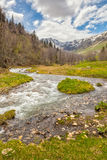 View to snow on Caucasus mountains over motion blurred stream ne Royalty Free Stock Photo