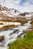 View to snow on Caucasus mountains over motion blurred stream ne Royalty Free Stock Photography