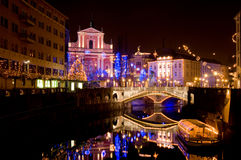 View to St. Francis church and Three bridges, with Ljubljanica river running below, decorated for New Years holidays Stock Photo