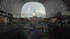 View to the stores and people in Market Hall, Rotterdam. ROTTERDAM, NETHERLANDS - AUGUST 05, 2016: Tilt shot of people shopping in the stores and riding