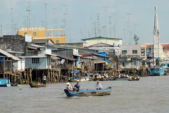 View To The Stilt Houses And People Crossing River By Boat In Cai Be, Vietnam. Stock Photo