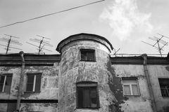 View to the top floor of an old, flaky house with a circular entrance and roof antennas. Black and white photo.  royalty free stock photography