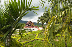 View to the traditional Thai temple in a garden through palm lea. Ves - beauty of architecture and nature Royalty Free Stock Images