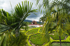 View to the traditional Thai temple in a garden. Through palm leaves Stock Image