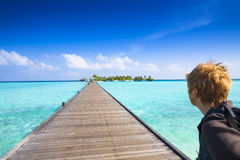 View to a tropical island. Womean looks from the jetty to a tropical island Stock Image