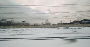Passing by winter city, view from moving train stock video