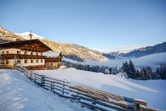 View to a winter landscape with old farmhouse and mountain range, Gasteinertal valley near Bad Gastein, Pongau Alps Stock Photo