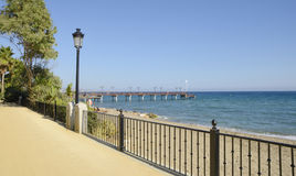 View to a wooden pier form the promenade beach Stock Image