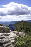 View from the Top. A couple of hikers take a rest at the top of mountain summit to enjoy the view and life royalty free stock images