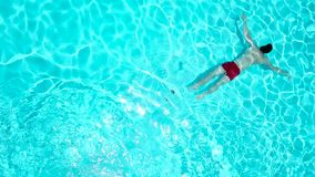 View from the top as a man dives into the pool and swims under the water. View from the top as a man dives into the pool and floats under the water stock video footage
