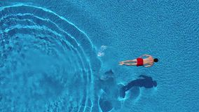 View from the top as a man dives into the pool and swims under the water stock footage