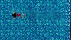 View from the top as a woman jumping and dives into the pool and swims under the water. Sporty female swimmer. aerial. View. Drone stock video