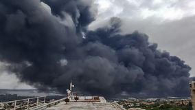Roof top view of black toxic smoke pollution. View from top of building of black toxic smoke from a factory fire polluting the atmosphere of Durban stock photography