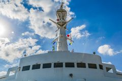 View of the top of the cabin of a ship with flags. Beautiful view of the top of the cabin of a ship with flags on a wonderful sunny day with an amazing blue sky royalty free stock image