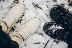 View from top at couple shoes in snow on ground in winter park. Hipsters shoes Royalty Free Stock Image