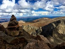 Mountain Top View with Cloudy Blue Sky. View from the top of a 14,000 foot tall mountain in Colorado, USA. A rock cairn is to the left framing the brown hills stock image