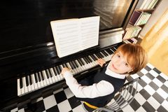 View from top of girl in uniform playing piano. View from top of beautiful small girl in school uniform playing the piano with notes during lesson indoors Royalty Free Stock Photography