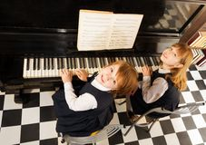 View from top of girls in uniforms playing piano