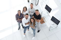 Group of creative professionals standing in office. View the top. a group of creative professionals standing in office and looking up Royalty Free Stock Image