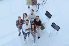 Group of creative professionals standing in office. View the top. a group of creative professionals standing in office and looking up Royalty Free Stock Photo