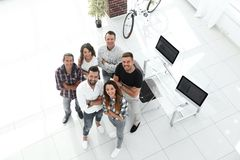 Group of creative professionals standing in office. View the top. a group of creative professionals standing in office and looking up Royalty Free Stock Photos