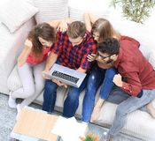 Group of friends looking at the photo on the laptop. View from the top. a group of friends looking at the photo on the laptop Royalty Free Stock Images