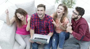 Group of friends watching a video on a laptop and laughing Royalty Free Stock Photo