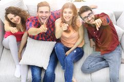 Group of laughing friends sitting on sofa and showing forefinger on the camera. View from the top.a group of laughing friends sitting on sofa and showing royalty free stock images