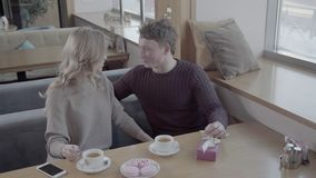 View from the top: a guy and a girl sitting at a table in a cafe near the window. Drinking tea and sweet talk. Loving couple in a cafe drinking tea on the stock footage