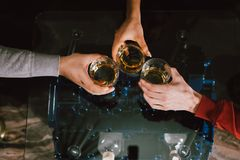 View from the top. Hands of people with glasses of whiskey or wine, celebrating and toasting of the wedding, meeting or other royalty free stock photo
