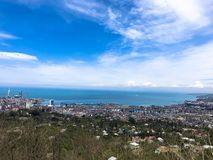The view from the top from a height of a beautiful tourist city with buildings and houses, roofs of trees and plants, nature stock photo