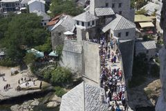 View from the top of the historic Mostar bridge full of people. MOSTAR, BOSNIA AND HERZEGOVINA - AUGUST 17 2017: View from the top of the historic Mostar bridge Royalty Free Stock Photography