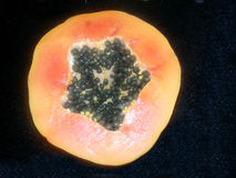 The view from the top. Juicy papaya is a breakdown on a black background. The view from the top. Juicy papaya in the cut with seeds inside on a black background Stock Photos