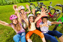 View from top of kids in helmets with hands up Stock Photos