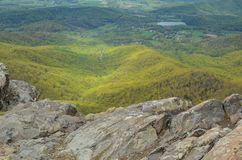 View from the top of Little Stony Man mountain in Shenandoah National Park on a foggy spring day. Focus on the rocks in foreground. Trees in valley royalty free stock photography