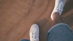 View from the top: The man in white sneakers goes through the desert stock video footage