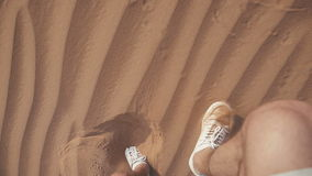 View from the top: a man in a white sneakers walks through the desert stock video