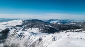 A view from the top of the mountain to the cliffs covered with snow and the pine valley with a clear blue sky on a sunny day stock image