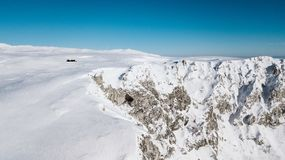 A view from the top of the mountain to the cliffs covered with snow on a sunny day stock image