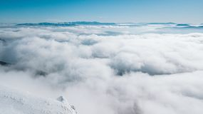A view from the top of the mountain to the valley covered with clouds with a clear blue sky on a sunny day stock photos