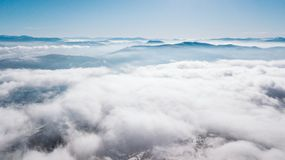 A view from the top of the mountain to the valley covered with clouds with a clear blue sky on a sunny day stock photography