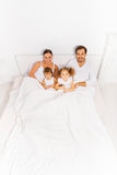 View from top of parents and two kids on white bed Stock Images