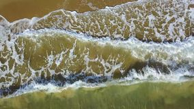 View from the top for a quick waves has reached the shore. Aerial survey. View from the top for a quick splashing sea waves has reached the sandy yellow shore stock footage