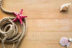 View from top on rope, seashells and starfish on wooden boards Stock Photo