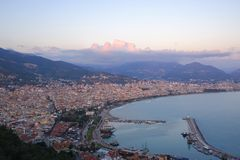 The view from the top on sea harbor city Alanya, Turkey. bay surrounded by mountains, over the mountains blue and pink clouds. View top sea harbor city alanya stock photography