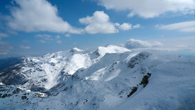 View from top of the ski-lift. At the top of the highest ski lift of the Vogel ski resort in Bohinj. Clear blue sky with some clouds in the distance. Mountain Stock Image